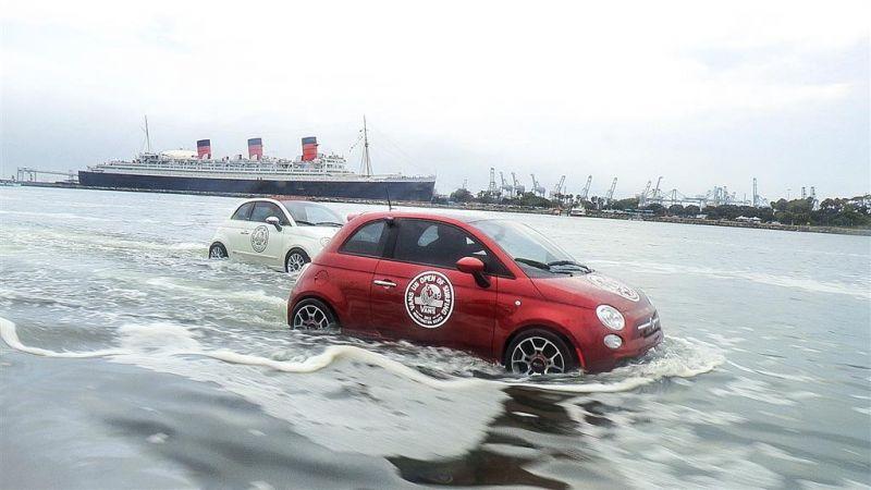 Fiat 500 in rot und weiß schwimmen vorm Huntington Beach