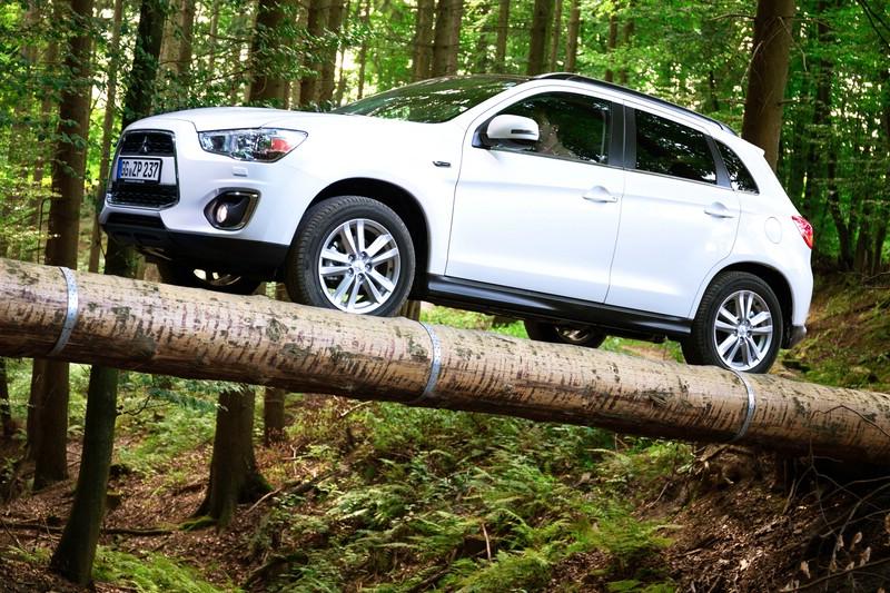 Mitsubishi ASX in weiß auf Baustamm im Wald