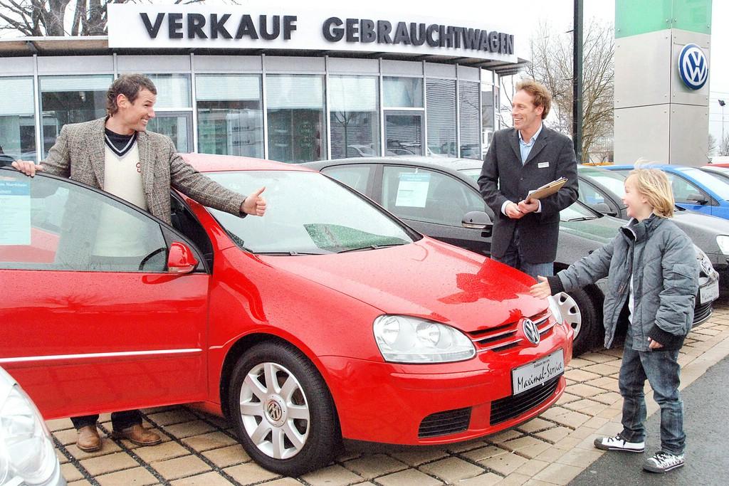 Eine Familie interessiert sich für einen gebrauchten Volkswagen
