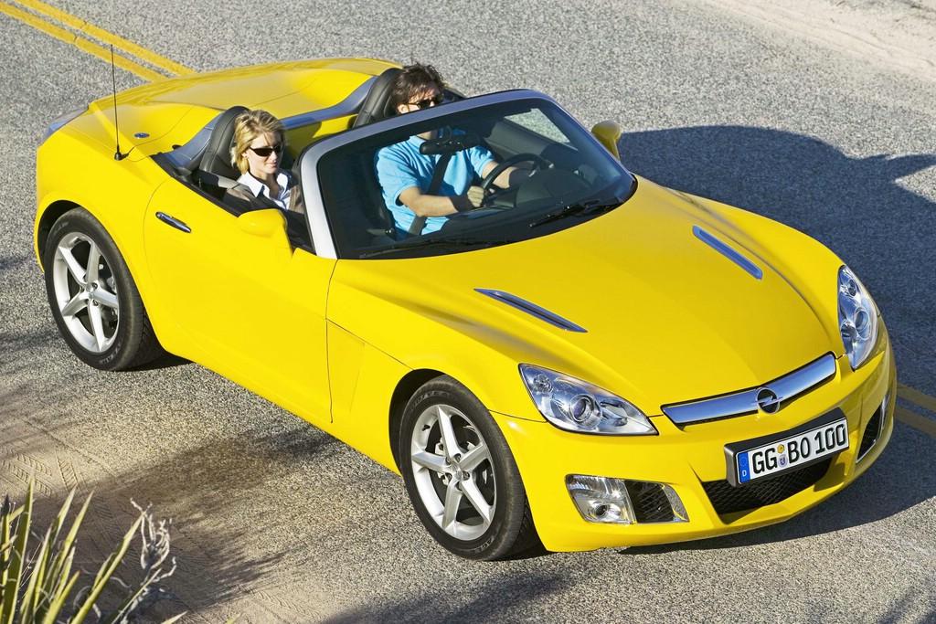 Gelber Opel GT mit Menschen an Bord
