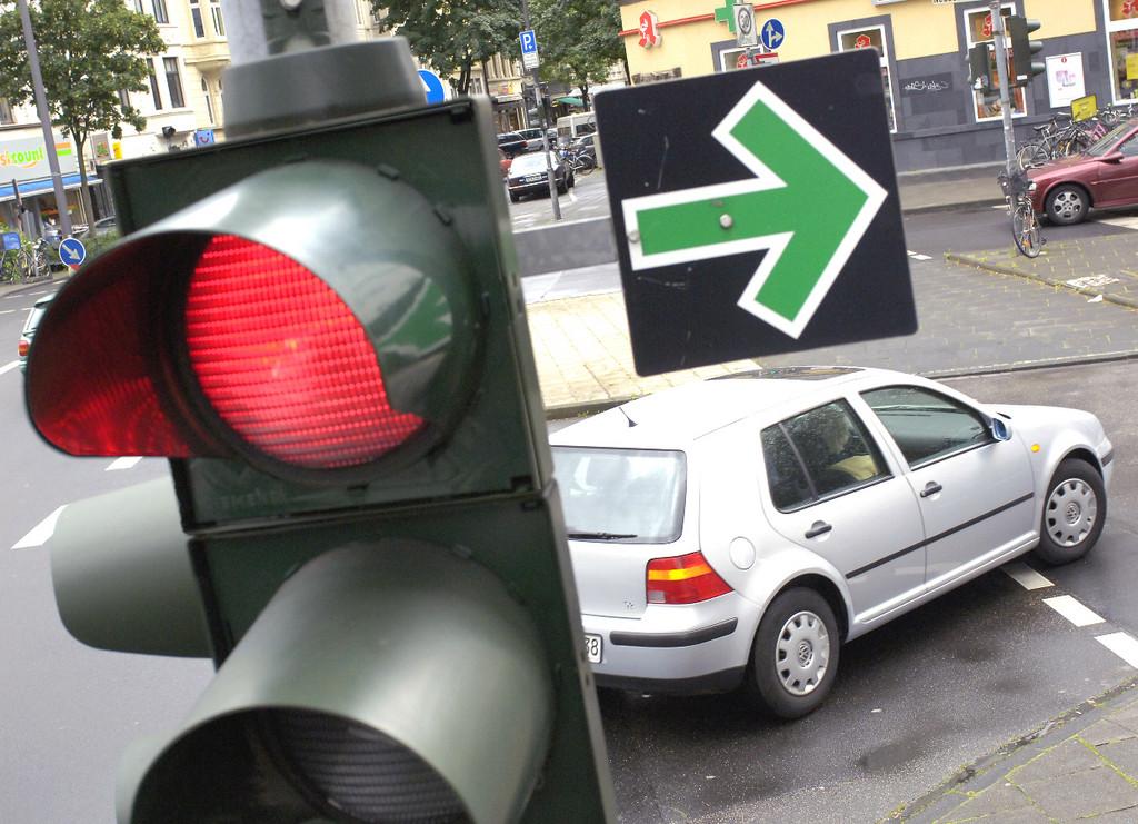 Grüner Pfeil am Ampelanlage die auf rot geschaltet ist
